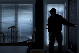 A burglar entering a home in the dark.