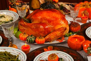 A turkey and other Thanksgiving dishes on a table decorated with pumpkins.