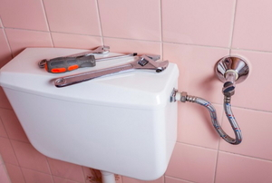 A toilet tank with tools on top and a pink tile wall.