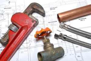 A copper pipe, wrench, valve, and bolts sit on top of construction plans.