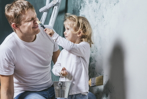 A young girl touches her dad's nose with a paintbrush.