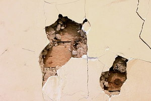 holes and cracks in a plaster wall