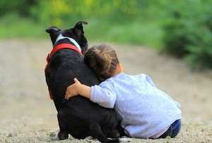 Child leaning on a black dog with a red collar