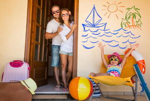 A family of three at a summer vacation house with pool toys and an ocean scene on the wall.