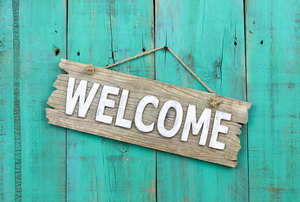 A wood welcome sign.