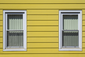 Yellow aluminum siding with two windows.
