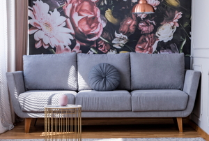floral wall with gray sofa and wicker table