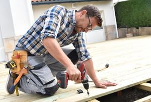man building deck with screwgun
