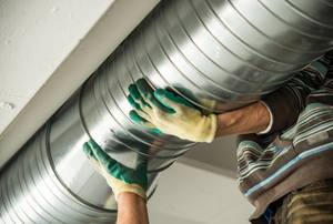 An HVAC worker installs heating ducting.