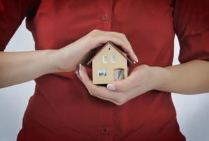 small house held in the hands of a woman