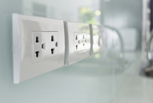 outlets on a kitchen wall near a sink