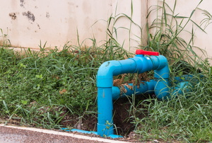 A blue sump pump in a grassy area against a white fence.