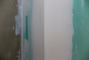 An outer corner formed from greenboard drywall.