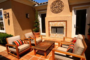 An earth-tone patio with a stucco fireplace.
