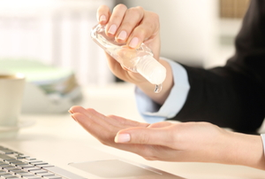 woman applying hand sanitizer in office environment with laptop