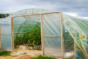 a greenhouse made from wooden frames and thin plastic