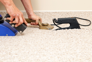 A carpet installer fixes the seam of a carpet using a carpet iron.