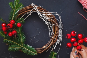 a grapevine wreath with evergreen and holly berries