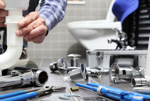 A man with tools works on a plumbing project.