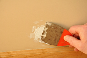 A man uses spackling compound on a wall