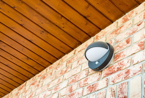 A motion sensor light mounted to a brick wall
