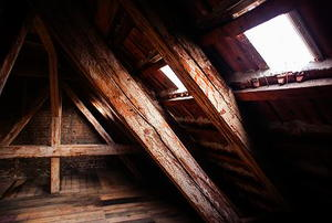 The corner of an attic with windows on the near wall.