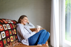 A woman sitting on a couch with a cup of tea, looking out a window.
