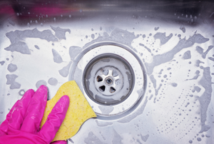pink glove holding a sponge and cleaning a sink