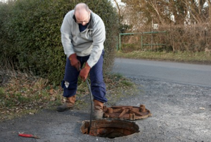 A man using a drain snake in a hole in the street