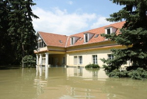 A home in a flooded area with water reaching up to the windows