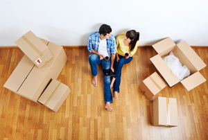 A couple sitting on the ground, surrounded by moving boxes.