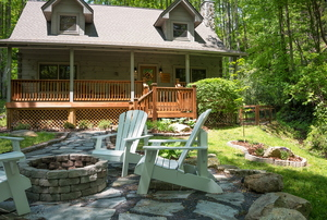 A cabin home with adirondack chairs around a fire pit.