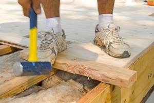 A construction worker working on the subfloor of a house.