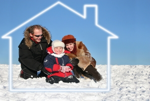 A family sits outside on the snow surrounded by the outline of a house.