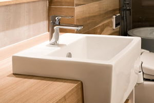 white bathroom sink set into a light wood countertop