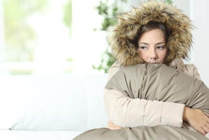 Woman in a coat squeezing a large pillow