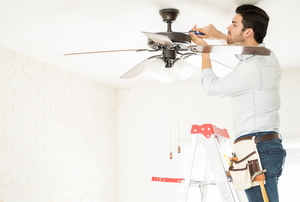 A man adjusts the settings on a ceiling fan.