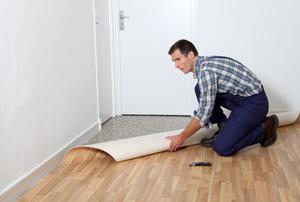 man rolling out linoleum flooring