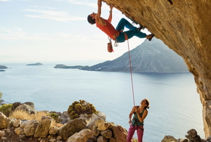 man and woman rock climbing with ropes in a beatiful coastal area