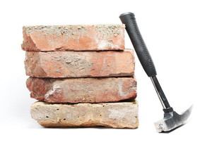 A brick hammer laying against a stack of bricks.