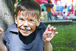 A boy with his face painted like a tiger