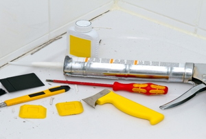 Caulking tools on a bathtub.