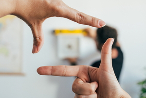 person's hands held up like a frame around another person hanging  picture