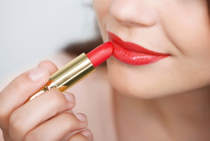 A young woman applying glossy red lipstick.