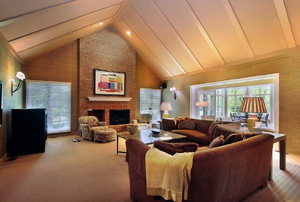 A family room with carpet and couches in neutral tones.
