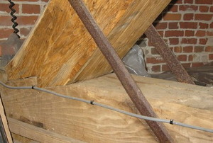 a triangular joint between two beams against a brick wall.
