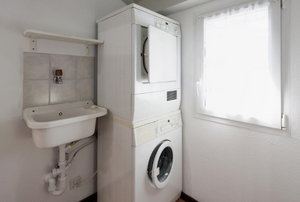 stackable washer and dryer unit in a bathroom