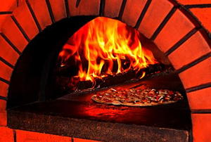 A pizza baking in a brick oven.