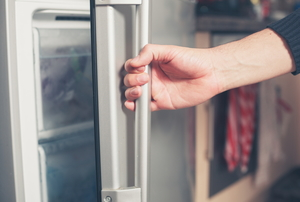 A woman opens a freezer door.