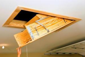 A hand pulling down a loft hatch.